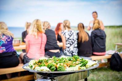 Sällskap som sitter och äter vid ett bord utomhus.
